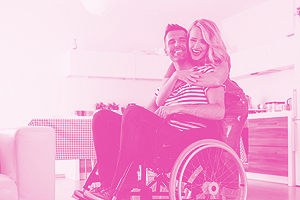 Happy disabled man sitting in a wheelchair in the domestic kitchen, his wife embracing him.